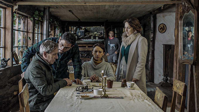 quatre personnes autour d'une table, deux assises et deux debout, l'air très inquiet