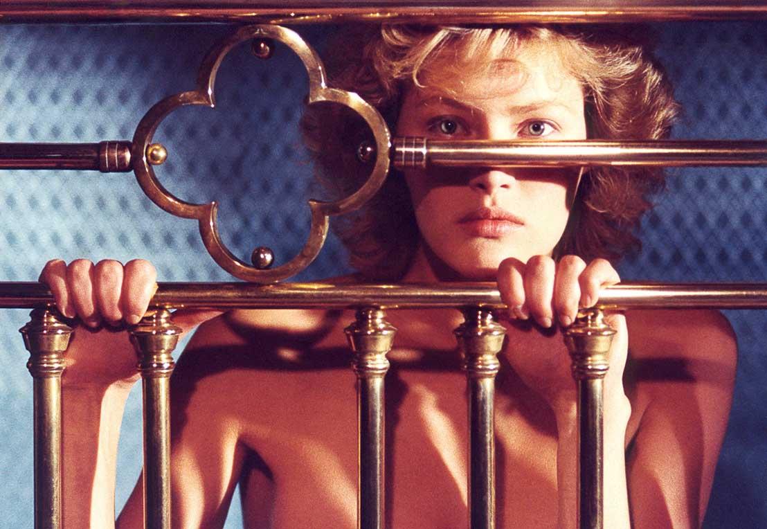 femme blonde nue derrière les barreaux de son lit