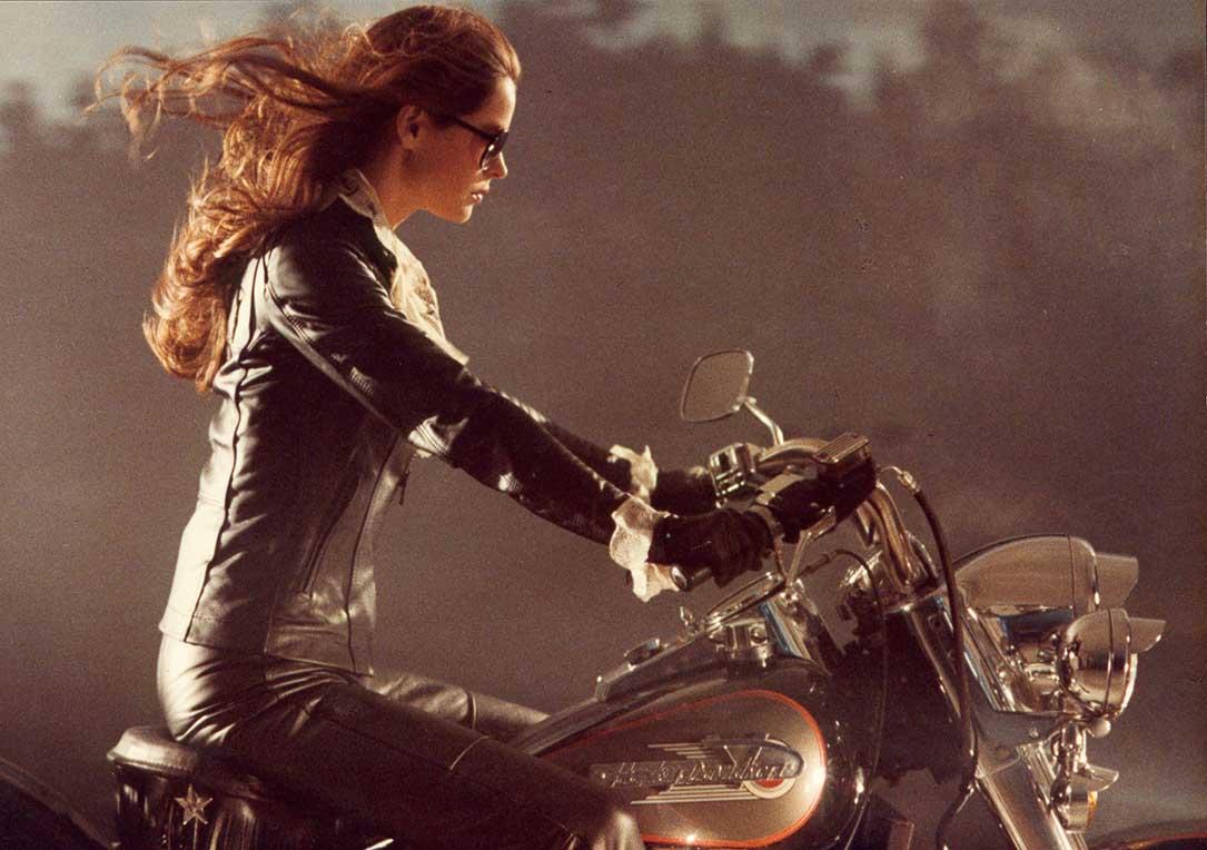femme brune habillée en cuir noir, sur une moto, les cheveux au vent