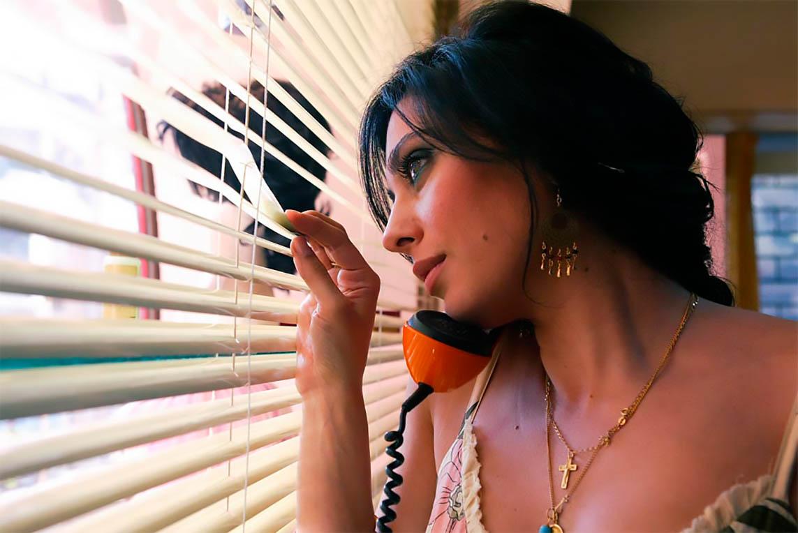 Femme qui regarde à travers des store un téléphone à l'oreille
