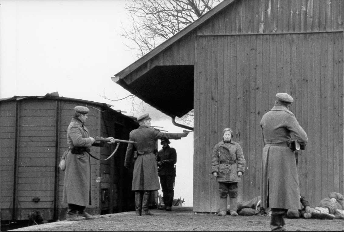 un femme devant trois soldat qui la tiennent en joue, pour l'exécuter
