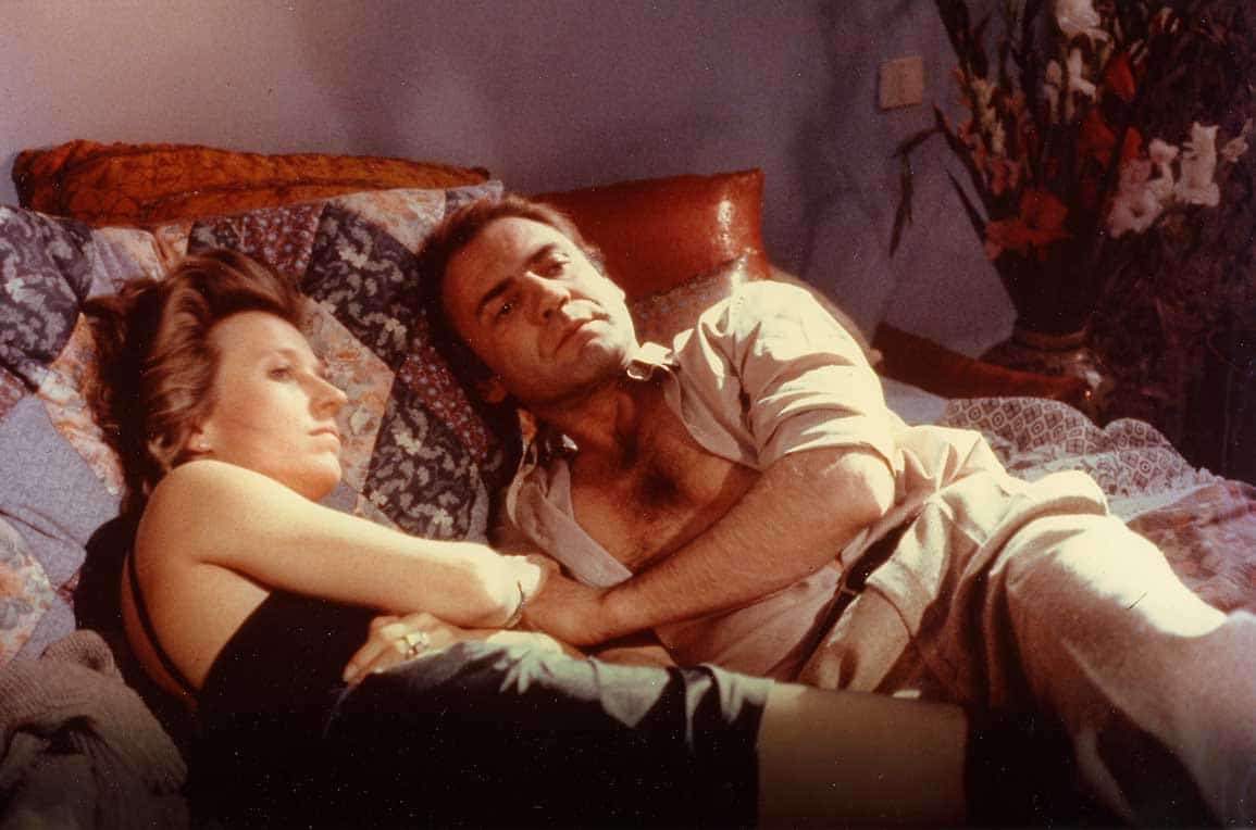 une femme et un homme habillé et couché sur un lit