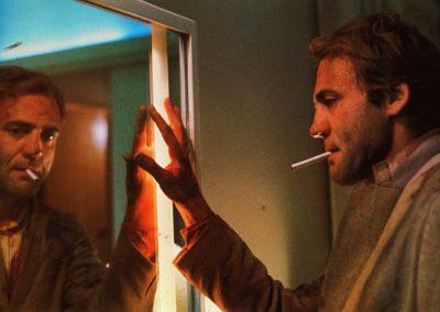 un homme avec une cigarette au bec,qui touche de sa main droite son reflet dans un miroir