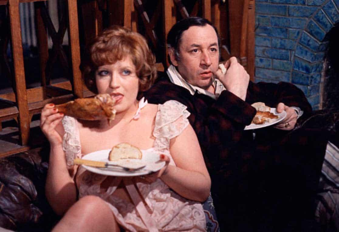 Andréa Féréol et Philippe Noiret qui mangent, assis dans un canapé.