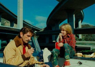 un homme et un petit grçon qui mangent un morceau dehors sur le bord de la route, sous un pont