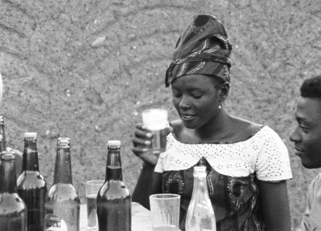 Femme africaine qui déguste une bière.