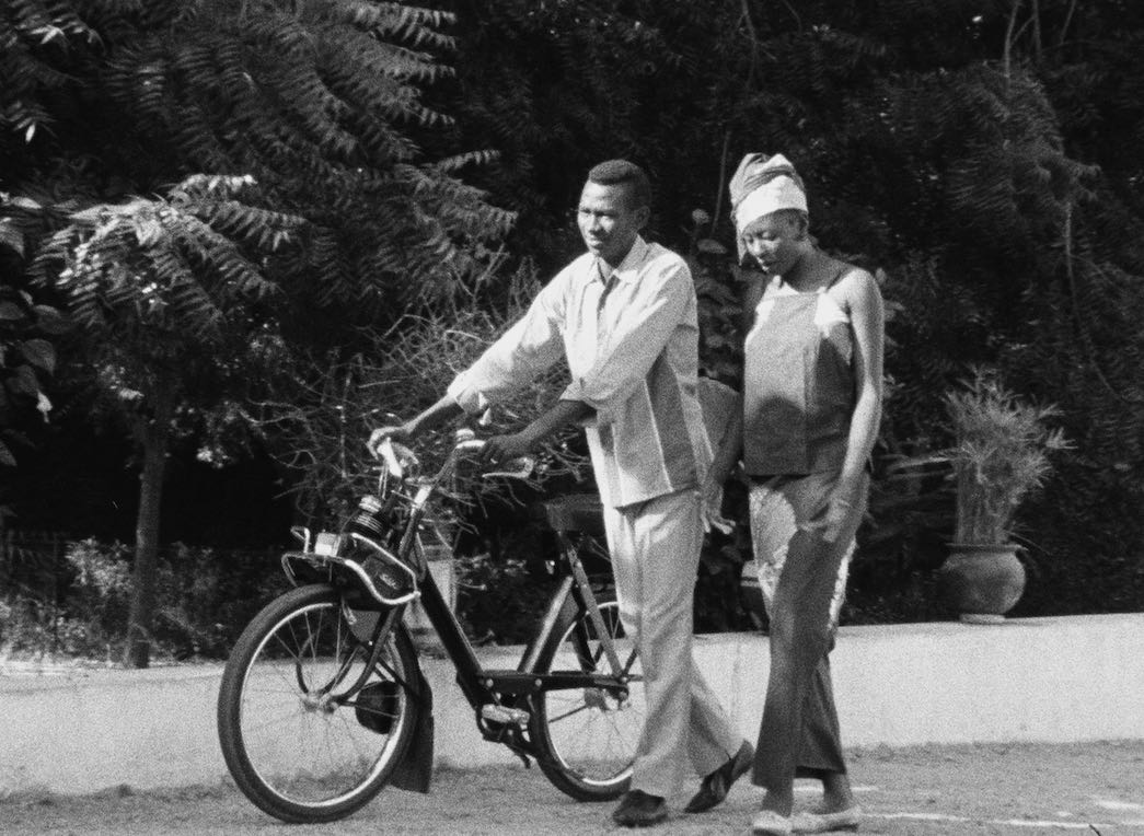 Homme qui pousse un vélo accompagné d'une femme