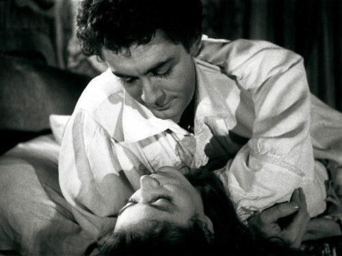 une femme couchée dans les bras d'un homme, ils se regardent langoureusement