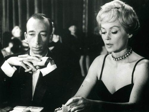 Une femme et un homme assis à une table, ils jouent au poker