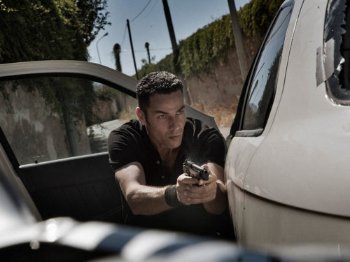 Homme près d'une voiture revolver à la main