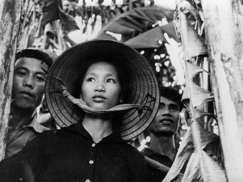 Une femme avec un chapeau vietnamien devant suivie de deux hommes