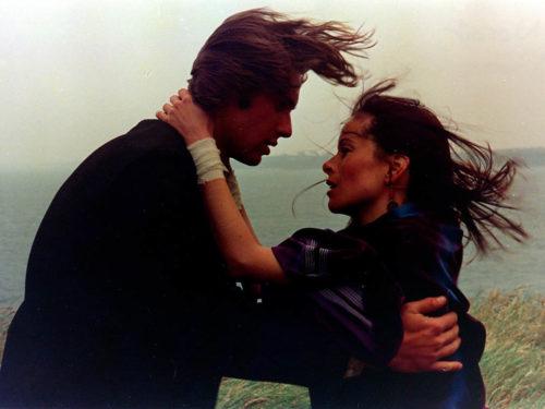 une femme et un homme qui se tienne et se regarde profondement, les cheveux dans le vent